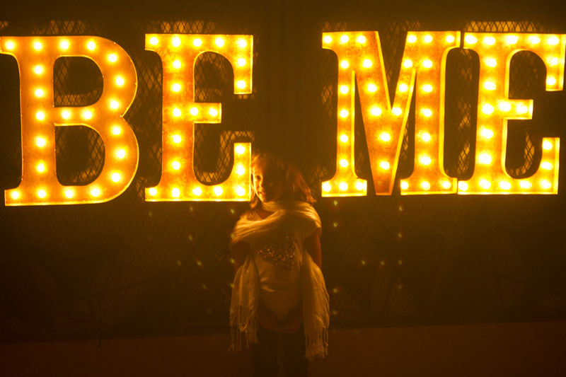 Little girls in front of sign that says Be Me.