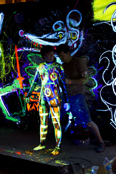 Human canvas with black light paint on them.
