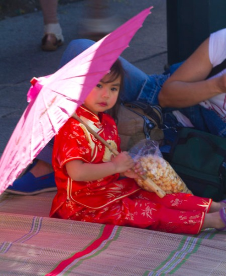 Small girl with parasol watching parade