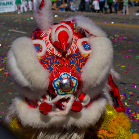 lion costume bending down in front of crowd