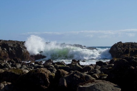 large wave breaking on rocks in background.