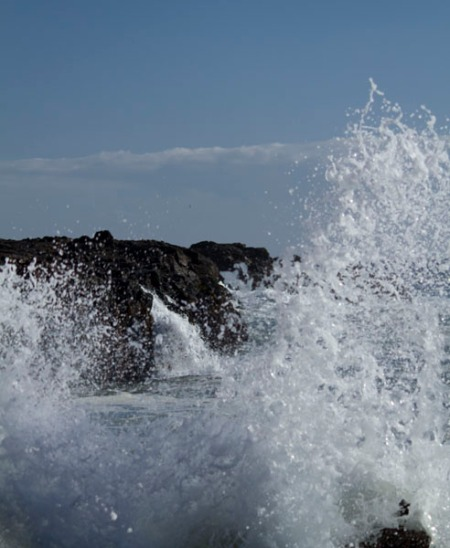 close up view of wave crahing on rocks