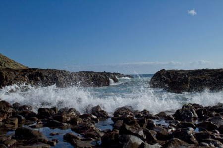 wave breqking on rocks in foreground