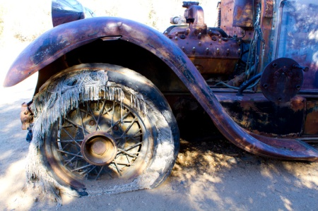 Close up of a wheel and fender of an old truck in the desert